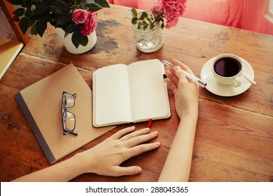woman at home writing and working with diary. Flowers, notebook, glasses and coffee at wooden table.