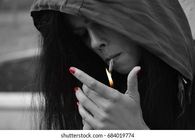 Woman in hood lighting a cigarette