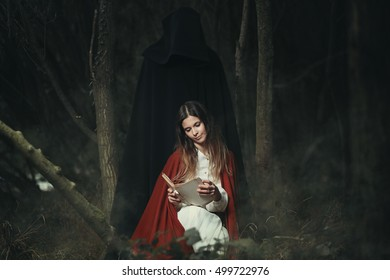 Woman with hooded figure at her back . Halloween and horror