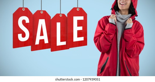Woman in hooded jacket standing against white background against blue background