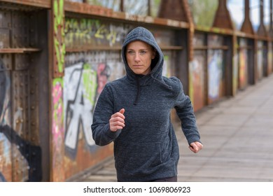 Woman in a hoodie jogging over an old bridge with rusted metal girders and colorful graffiti on the walls approaching the camera in a health and fitness concept
