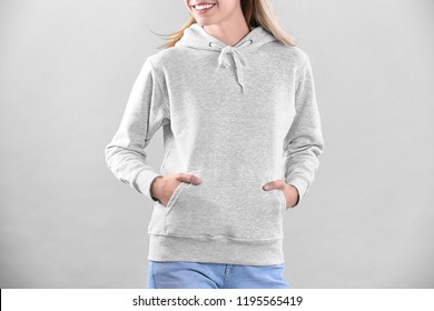 Woman in hoodie sweater on light background. Space for design