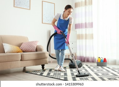 Woman hoovering carpet in living room. Cleaning service