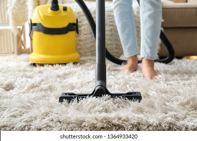 Woman hoovering carpet with vacuum cleaner