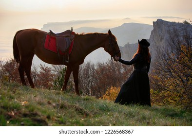 Woman and horse are standing in the beautiful autumn forest on the background of the evening mountains