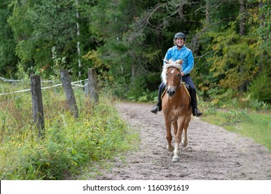 Woman horseback riding on country