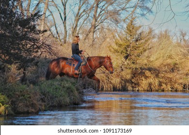 Woman horseback riding through a creek