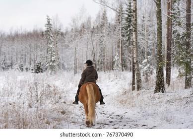Woman horseback riding in winter