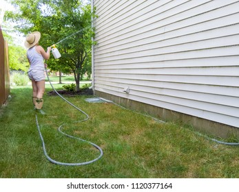 Woman hosing down the sides of her house with a handheld pressure sprayer attached to a hosepipe