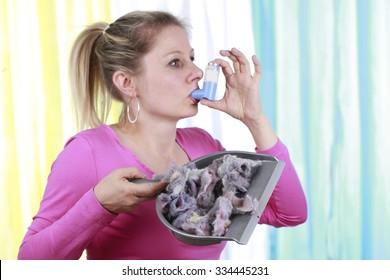 Woman with house dust allergy using asthma spray