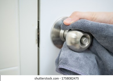 Woman house keeper cleaning a dirty stainless door knob in toilet. Maid spraying liquid cleaning solution on the dirty door knob handle in toilet and using micro fabric wipe on door knob surface.