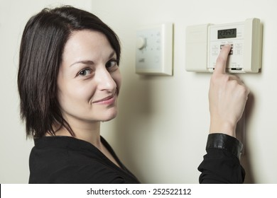 A woman in house who set is thermostat.