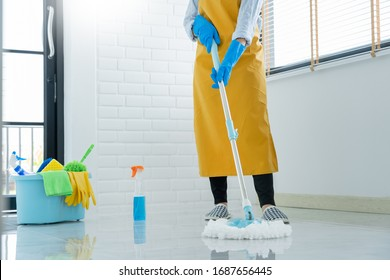 Woman housekeeper with mop and bucket with cleaning agents for cleaning floor at home, Floor care and cleaning services