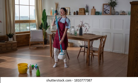 woman housemaid wash floors with mop and dance because she is happy
