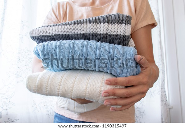 Woman, housewife holding a stack of clothes in hands close up.