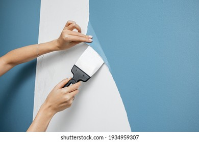 A woman housewife peels off an old vinyl wallpaper with a trowel or spatula