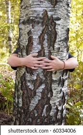 woman hugging birch tree