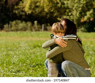 A woman hugging a boy in a field.