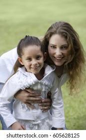 woman hugging girl at lakeside park