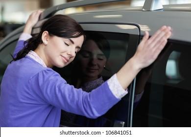 Woman hugging a grey car in a car dealership