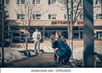 """A woman is hugging her adopted little son and her husband is waiting them with toy.  There is a sign """"Orphanage"""" on russian language on the building behind them. Image with selective focus and toning"""