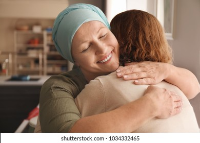 Woman hugging her mother with cancer indoors