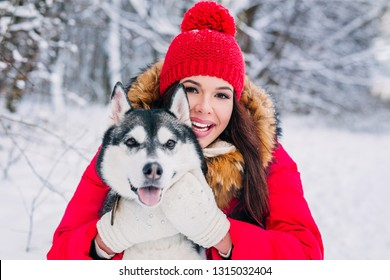 Woman hugging the Husky dog in winter forest