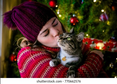 Woman hugging and kissing her cat with a christmas atmosphere.
