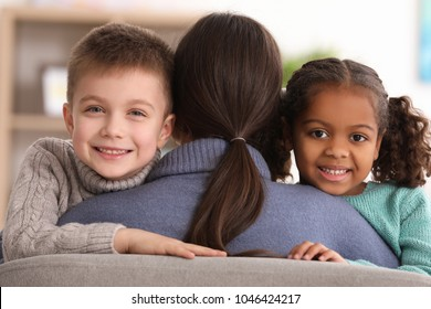 Woman hugging little kids indoors. Child adoption