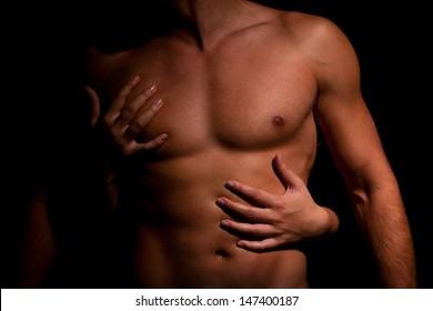 Woman hugging muscular man on a dark background