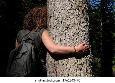 Woman hugging a tree with kindness