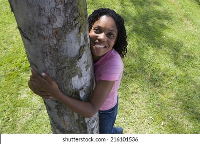 Woman hugging tree trunk