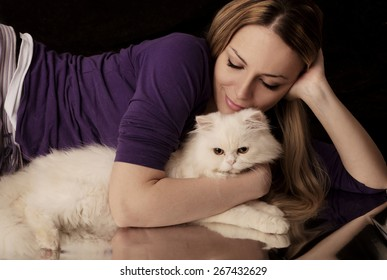 Woman hugging white cat