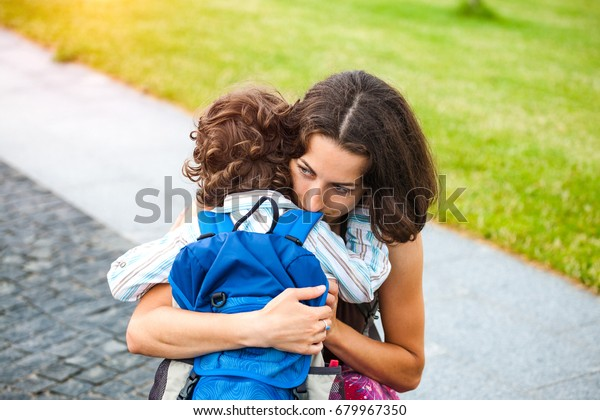 A woman hugs a curly-haired boy and smiles. Mom feels sorry for her son. Meeting mom and baby after separation. A child with a backpack hugs her mother.