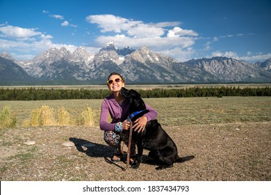 Woman hugs and holds her black labrador retriever dog in front of the Grand Teton National Park mountains in Jackson Wyoming as the dog licks her face
