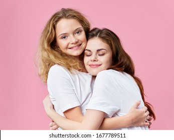 Woman hugs little daughter on a pink background