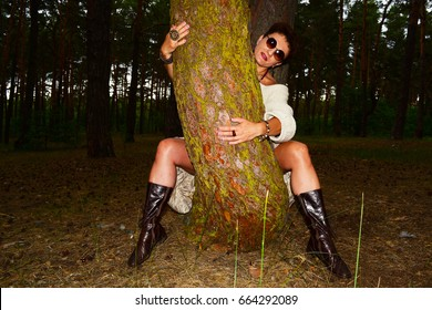 A woman hugs a pine tree, sitting among the trees in the forest
