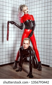 Woman humiliates a man. Woman and man dressed in latex suits. A woman humiliates a man. Style of submission and BDSM.