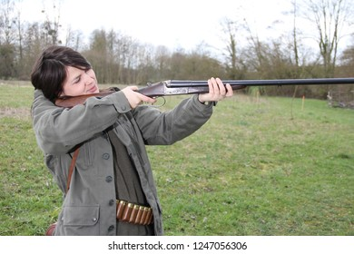 woman hunter with shotgun aiming.