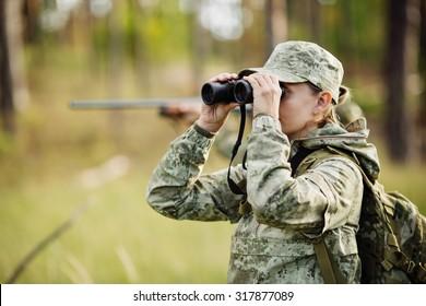 woman hunter with shotgun looking through binoculars in forest