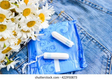 Woman hygiene protection, close-up.panty liners and tampons on jeans background.white daisy flowers, women's health.feminine pads.critical days