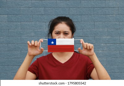 A woman and hygienic mask with Chile flag pattern in her hand and raises it to cover her face. A mask is a very good protection from Tiny Particle or virus corona or Covid 19.