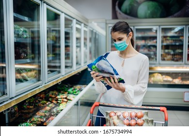 Woman with hygienic mask shopping for supplies.CPandemic quarantine preparation.hoosing nonperishable food essentials from store shelves.Budget buying at a supply store.Food supplies shortage.