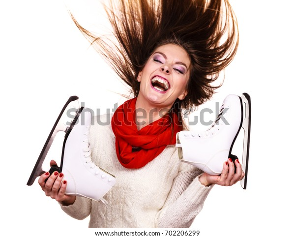 Woman with ice skates getting ready for ice skating, winter sport activity. Smiling cheerful girl with blowing hair wearing warm clothing on white