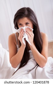 Woman ill in bed with a seasonal cold and flu