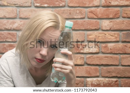 A woman is ill with a bottle of water. The concept of poisoning, a woman's hangover, migraine, headache.