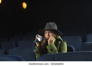 Woman  is illegally copying the movie in the cinema