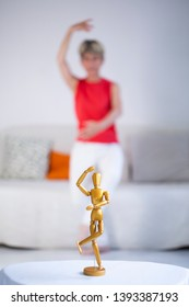 Woman imitating movements of dance of a wooden model.