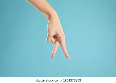 Woman imitating walk with hand on light blue background, closeup. Finger gesture