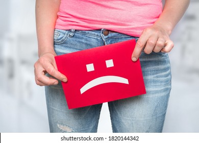 Woman with incontinence problem with sad smiley on paper - urinary incontinence concept
